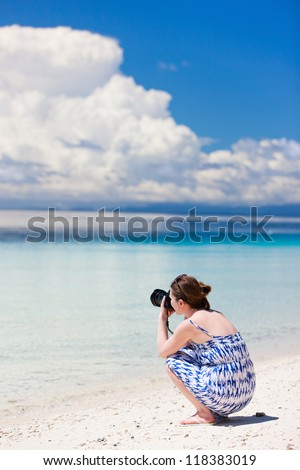 Young woman taking photos at a tropical beach