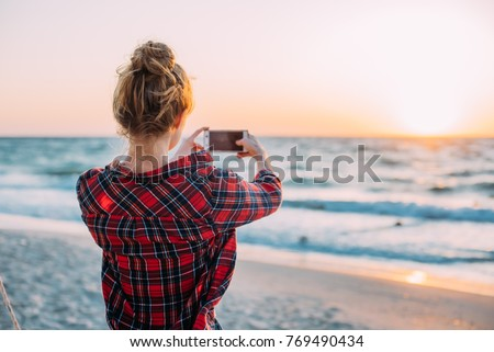 young woman taking photos with her smartphone on beach during sunset or sunrise