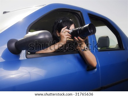 young woman taking photos with telephoto lens - illustrating surveillance - stock photo