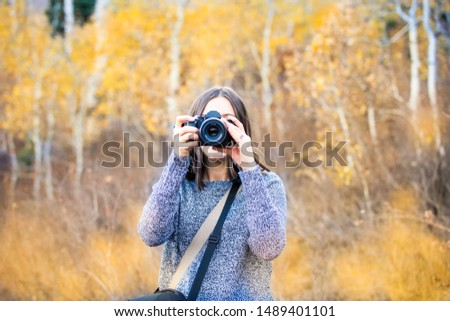 Young woman taking picture with black camera amid yellow leaf aspen trees, Utah