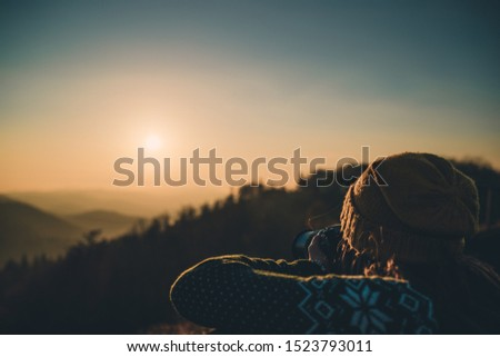 Young Woman Taking Pictures of Sunlit Fall Mountain Landscape form the Top. Hiker Girl is Taking photos with digital camera of beautiful autumn hills landscape at sunset, Lens Flare.