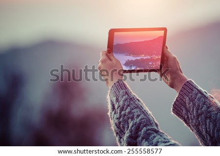Young woman taking pictures on a tablet in mountains at sunset. Toned picture