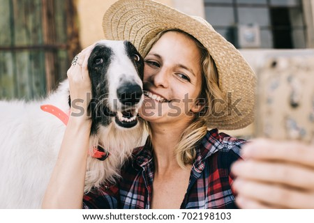 Young woman taking self portrait wit her dog for social media profile picture