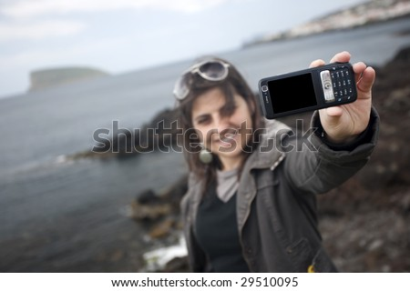 young woman taking self portrait with mobile phone camera - travel concept