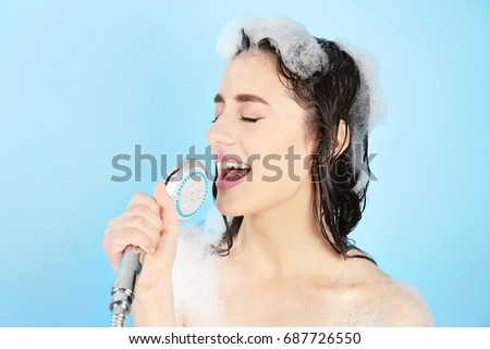 Young woman taking shower and singing on blue background