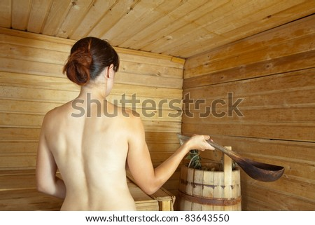 Young woman taking  steam bath in sauna