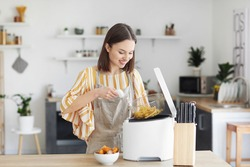 Young woman taking tasty french fries from deep fryer in kitchen