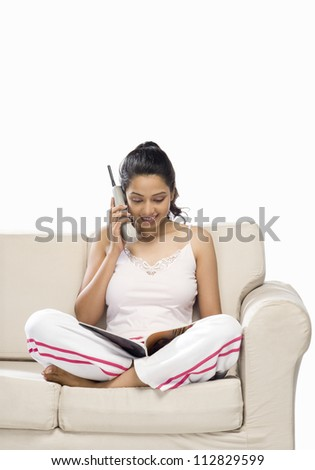 Young woman talking on a cordless phone and looking at a magazine