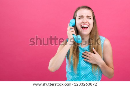 Young woman talking on an old fashioned retro phone on a pink background #1233263872