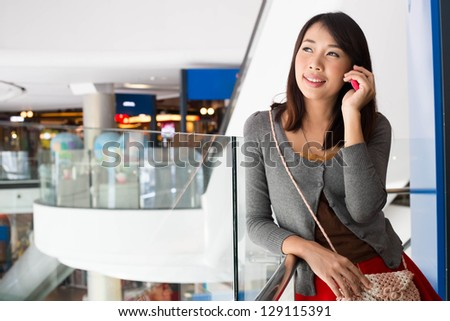 Young woman talking on mobile phone  in shopping mall