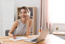 Young woman talking on mobile phone while working with laptop at desk. Home office