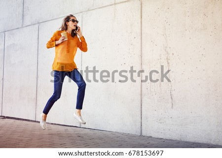 Young woman talking on phone and drinking coffee while rushing to work