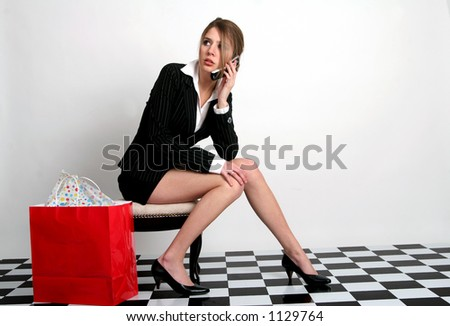 Young woman talking on the cellphone while sitting with a red bag next to her