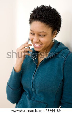 Young woman talking on the phone looking pleased.