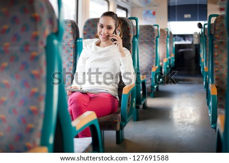 Young woman talking on the phone on the train