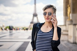 Young woman talking with mobile phone in front of the Eiffel Tower. Paris, France. Filtered image.