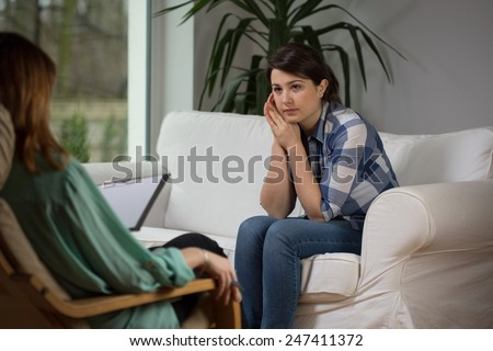Young woman talking with psychologist about her problems
