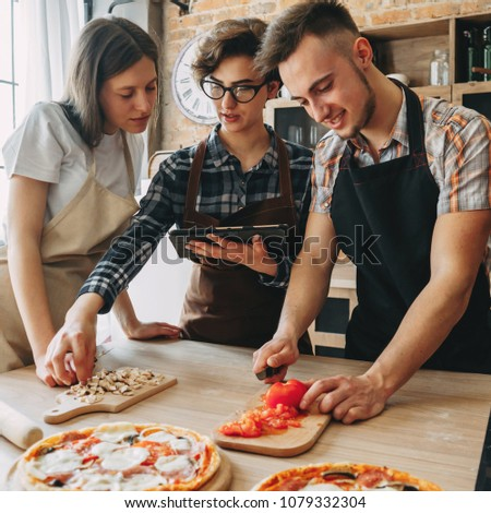 Young woman teach her friends how to cook food. People cooking pizza at kitchen together, reading recipe at tablet pc. Culinary, togetherness, friendship concept