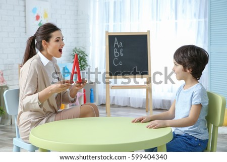 Young woman teacher and little boy on private lesson #599404340