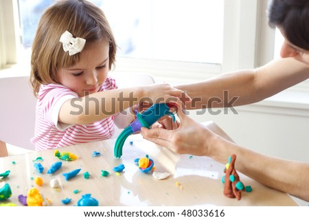 Young woman teaches little girl to use play dough