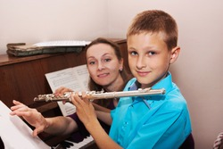young woman teaching a boy to play the flute at the music school
