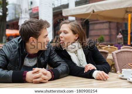 Young woman teasing man while sitting at outdoor restaurant