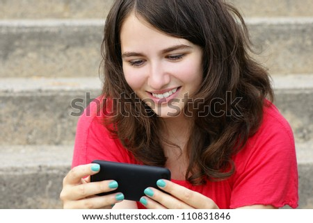 Young woman, teenager girl or student reading text on her cell phone and smiling, perfect for social media, networking or other internet technology.