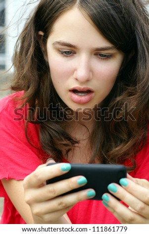 Young woman, teenager girl or student shocked at what she is reading on her cell phone