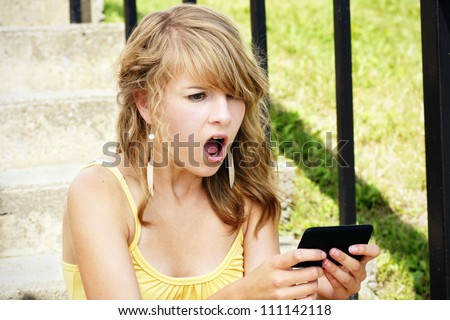 Young woman, teenager girl or student shocked at what she is reading on her cell phone, perfect for online intimidation or bullying at school.