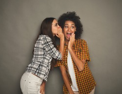 Young woman telling her girlfriend some secret. Two women gossiping. Excited emotional girl whispering to her friend ear, gray studio background