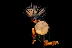 young woman Teotihuacana, Xicalanca - Toltec in black background, with traditional dress dance with a trappings with feathers and drum