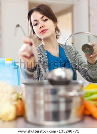 young woman tests  food with ladle in the kitchen
