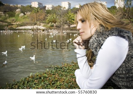 Young woman thinking of a duck pond