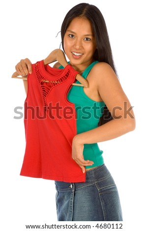 Young woman thinks whether to by new red top