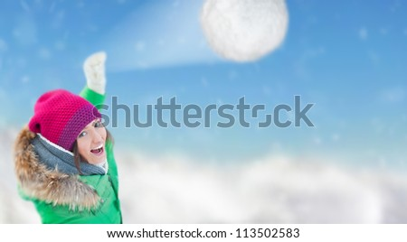 Young woman throwing a snowball. Winter fun concept