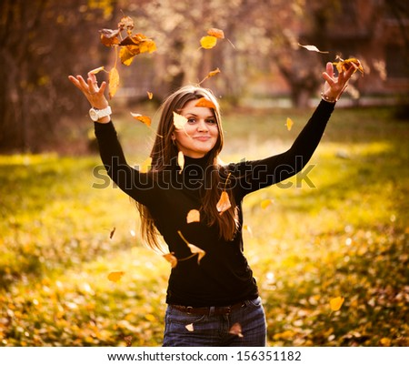 young woman throwing leaves woman in the forest