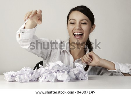 young woman throwing paper ball at someone or something having fun at her work desk