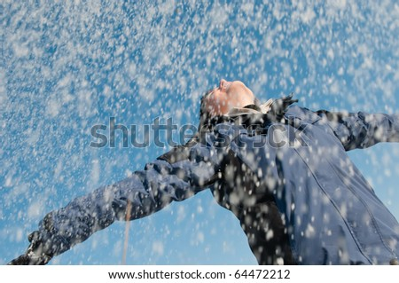 Young woman throwing snow on blue sky in background - joy and happines emotions