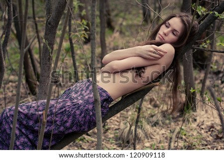Young woman topless hiding her naked chests under her arms in a forest
