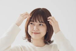 young woman touches her bangs