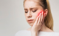 Young woman touching her cheek, having strong toothache and suffering from pain, empty space