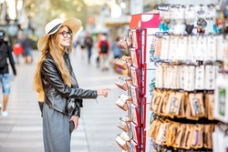 Young woman tourist choosing souvenirs on the central shopping street in Barcelona