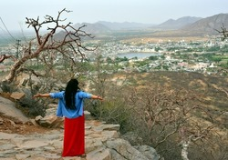 Young  woman tourist enjoying nice view of Holy Hindu Pushkar town in Rajasthan India from Neighboring hill