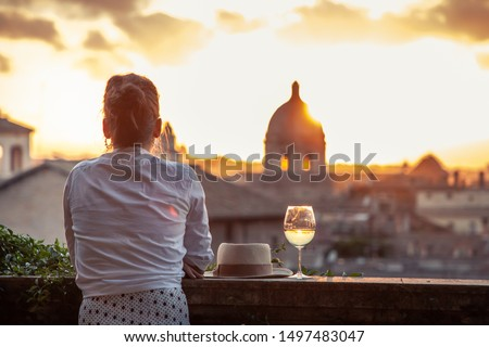 Young woman tourist fashion white dress with glass of white wine in front of panoramic view of Rome cityscape from campidoglio terrace at sunset. Landmarks, domes of Rome, Italy. Stock photo ©