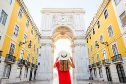 Young woman tourist in red dress standing back in front of the famous triumphal arch in Lisbon city center in Portugal