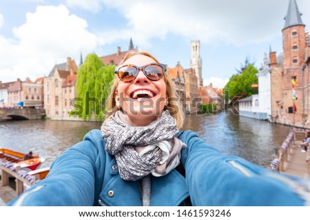 Young woman tourist is having fun, smiling and rejoicing while seeing the sights of Bruges, Belgium. Travel to Belgium. Happy girl makes selfie on the background of the famous viewpoint in the #1461593246