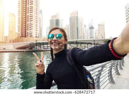 Young woman tourist laughing and taking selfie photo in Dubai Marina,Dubai,United Arab Emirates. Female traveler and photographer takes picture for her blog.Young happy tourist making selfie photo