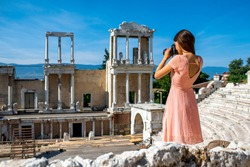 Young woman tourist photographing Roman theater of Philippopolis in Plovdiv, Bulgaria