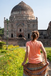 Young woman tourist poses and holds her skirt at the Tomb of Sheesh Gumbad tomb in Lodi Gardens in New Delhi, India