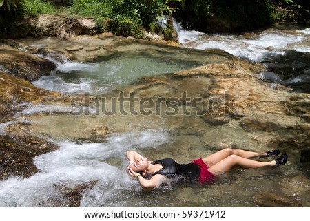 Young woman tourist relaxes in a shallow pool of water at the Dunn's River Falls in Jamaica.